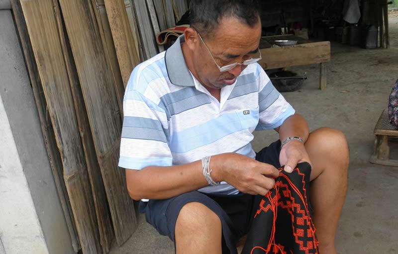 プリーツスカート用の長い布に刺繍をするモンの男性